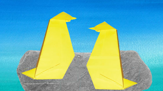 Two origami penguins sit on a rock, against a watercolor-painted sky.