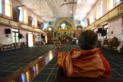 The sanctuary is empty, but for this woman sitting in one of the few pews in the wide open room.