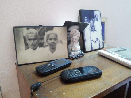 Two mobile phones sit atop a side table in front of framed pictures of elder family members.