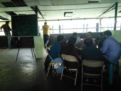 A group of people sits in folding chairs around a table. A callkboard full of writing stands to their right.