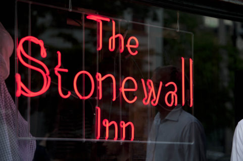 The Stonewall Inn is illuminated in red neon letters in the window of the Stonewall Inn. The checkered dress and puffy-sleeved blouse that Dorothy wore in the Wizard of Oz is just barely visible behind the window.