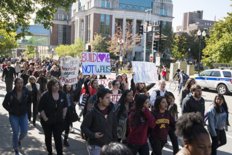 """A photograph of protesters of a range of races and genders marching with signs at the University of Minnesota. Some protesters are chanting. Some also wear University of Minnesota clothing. One sign reads """"1st gen American against racism"""" and two others read """"build love not walls."""""""