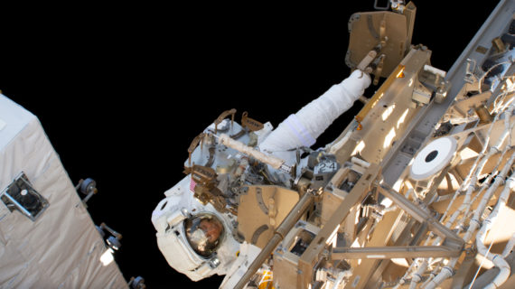 An astronaut in a space suit appears to be tinckering with the outside of a satellite, both floating in outerspace.