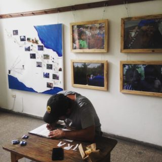 A man is hunched over a desk at the front of a room, cutting letters for what are likely stencils. The letters T-R-A are beside the paper the man is hunched over. On the wall behind him is a map of southern Mexico and Central America showing photos and a hand-drawn path.