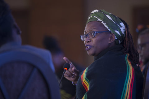 An African woman with glasses turns over her shoulder to a microphone , her right index pointing as she speaks. Her head is wrapped in a floral print, and her dredlocks are visible in the back.
