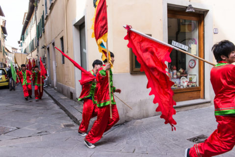 The youths all appear to be men. They wear bright red regalia with green trim. The red of their clothing matches the red of the trangle-shaped flags that they are carrying. In the photo, three men hurriedly round a corner, with many more behind them, all walking through narrow, stone-paved streets.
