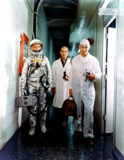 Three men stand side my side in a narrow hall. One wears a shiny space suite while the others appear to be in white lab coats.