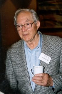 A pale man with classes and receding white hair wears a checkered suitjacket holds a cup of coffee. He has a nametag pinned to his collar.