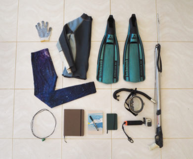 The contents of the bag are laid out on a square-tiled floor. Contents and bag are described below.