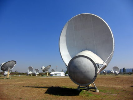 A field of satellites dot an arid field. The sky above is clear.