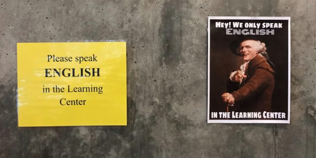 "The photograph displays two signs. The sign on the left has a yellow background and black letters that read ""Please speak ENGLISH (in all caps) in the Learning Center."" The sign on the right is a photograph of a man, possibly of Anglo-Saxon descent, who is wearing Renaissance-style clothing and smiling. He is pointing at the viewer and the accompanying text reads, in all caps, ""HEY! WE ONLY SPEAK ENGLISH IN THE LEARNING CENTER."""