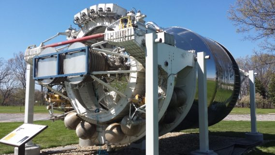 The engine is held up by three iron rods on each side. All of which reside in what seems to be an open-air museum.