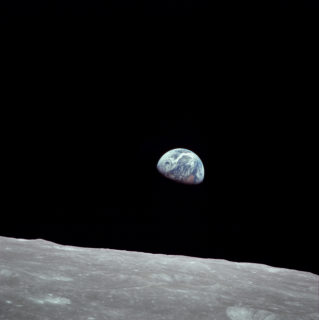 Photo of the earth from the surface of the moon. The earth looks half-full.