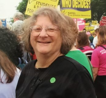 A white woman with glasses smiles at the camera. She wears a black t shirt and a round green pin.