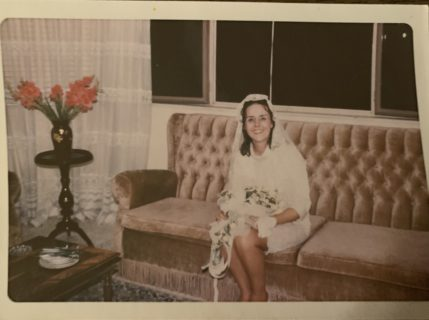 A woman with pale skin and dark brown hair sits on velvet a sofa. There are lard flowers of the sidetable to the left, and a window showing the night sky behind the woman. she appears to be in a knee-length wedding dress.