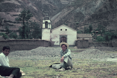 A small chapel sits at the base of a mountain. In front of it two men, one a white foreigner and the other a dark-skinned man, sit crossed legged on the ground.