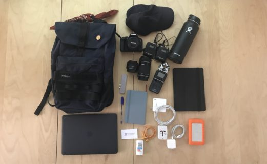 Contents of the a bag are laid out on a wood-paneled floor. The bag and its items are described below.