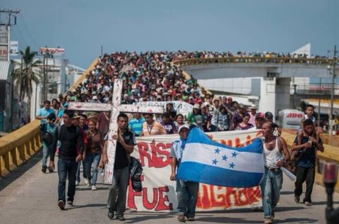 Thousands of people walk toward the camera over a white highway bridge. The people in front carry the national flag of Honduras, a cross that's taller than the person carrying it, and a banner whose words are obscured by the men carrying the flag.