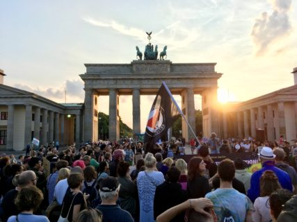 A crowd stands in front of Brandenburg Gate with the sun setting behind the gate