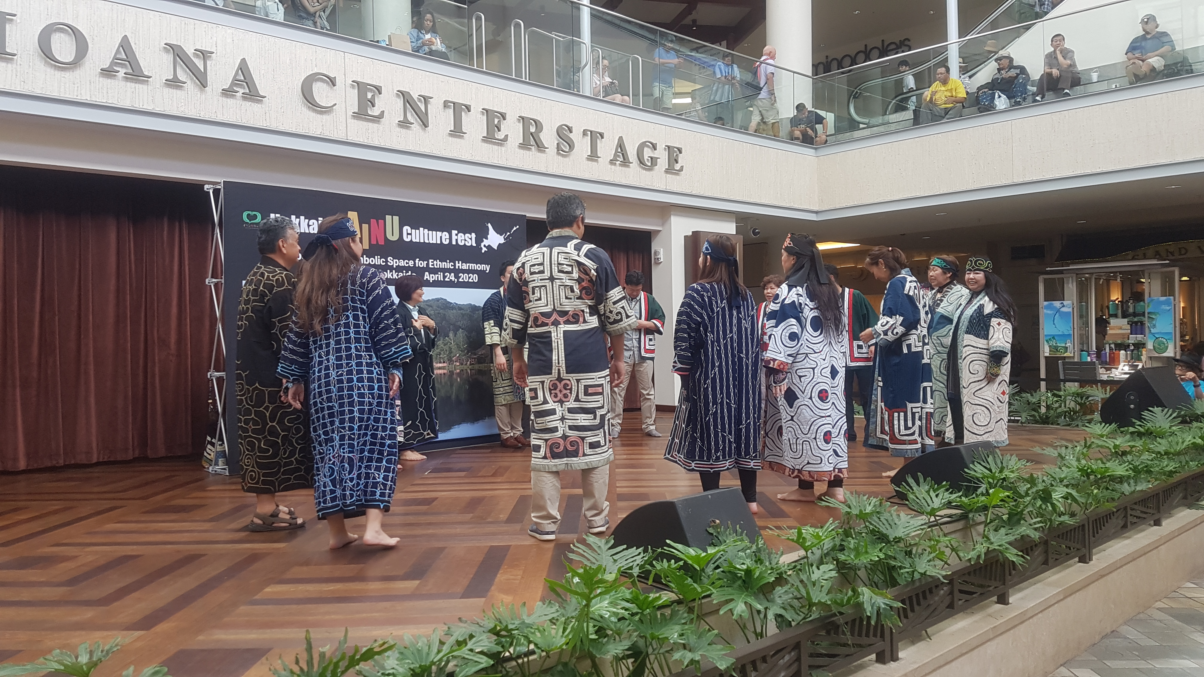 "About thirteen men and women dressed in traditional embroidered dark blue robes form a circle on a wooden stage with the words ""Ala Moana Centerstage"" on the second floor overhang. The words are cut off and only ""centerstage"" can be seen. Some audience members are looking at the performance from the second floor of the mall."