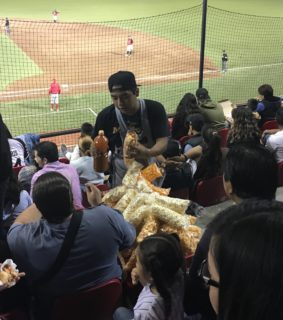 A concession vendor selling nuts and popcorn with baseball players in the background.