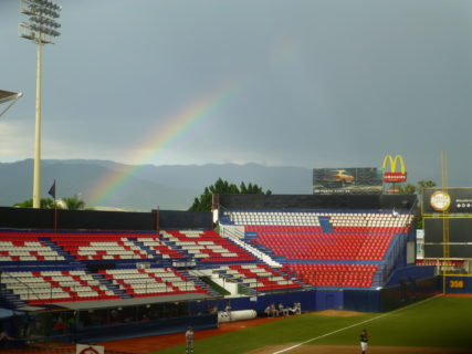 Baseball stadium bleachers with rainbow and McDonalds sign in the background.