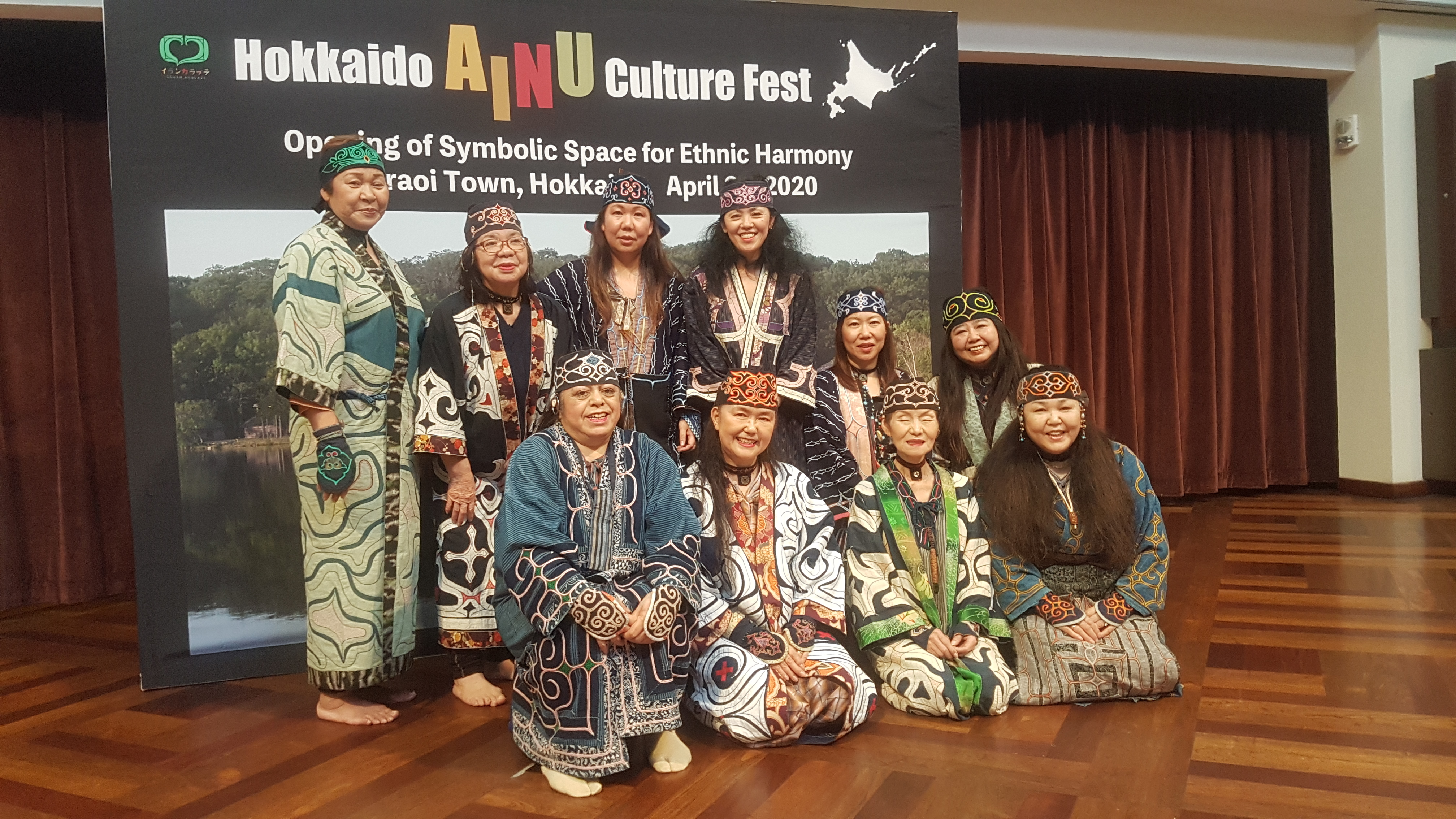 "The ten women from the performance group poses on the stage, in front of a poster with the words ""Hokkaido Ainu Culture Fest."" Words in smaller fonts, with parts blocked by the standing performers, read ""Opening of Symbolic Space for Ethnic Harmony, Shiraoi Town, Hokkaido, April 24, 2020."" The back row has four women standing and two kneeling on the right, and the front row has four women kneeling. They are dressed in dark blue robes embroidered in colorful threads and cloths."