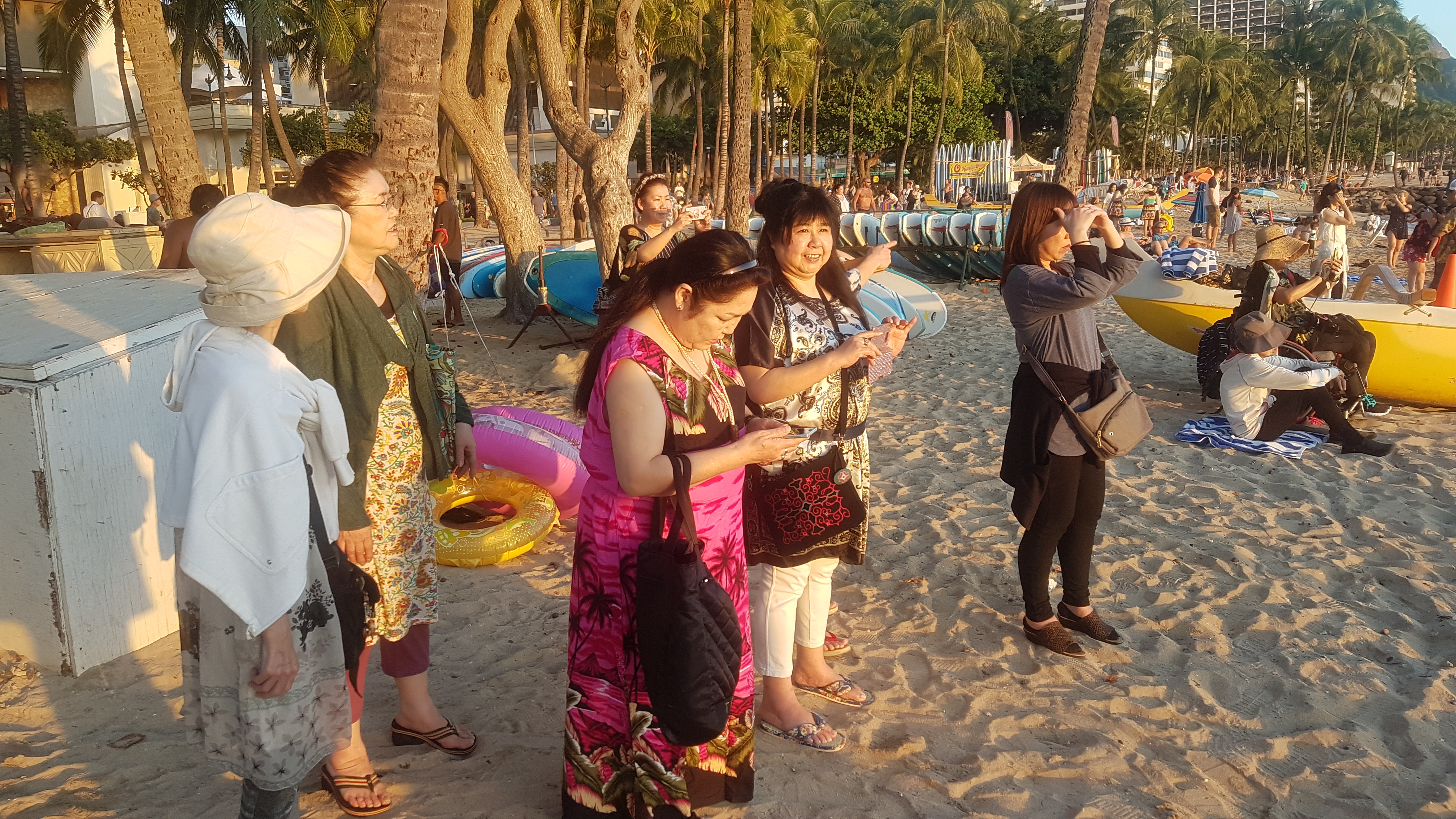 Six women dressed in summer wear on a beach with trees, surfboards and other tourists in the background. Some are gazing at the sea while some are in various stages of taking photographs with their mobile phones. The setting sun lights up their faces.