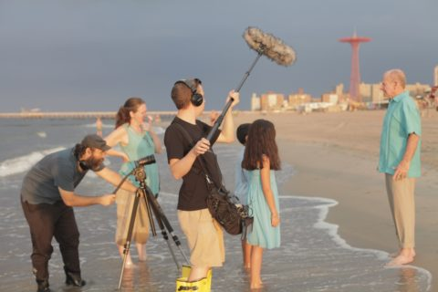 Two children and two adult actors stand in the edge of the ocean on a beach. A film crew with camera and sound boom film them.