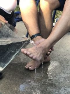 Photo of one hand lifting someone's foot and pouring water from a pitcher over it.