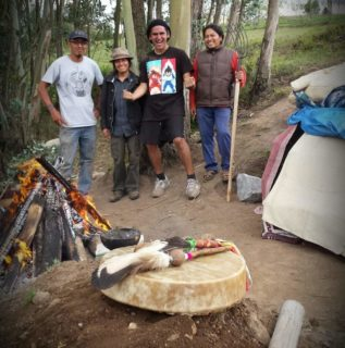 A photo of four people standing in the background with trees behind them. The foreground includes a small fire, caribou hand drum, and part of what appears to be tent.
