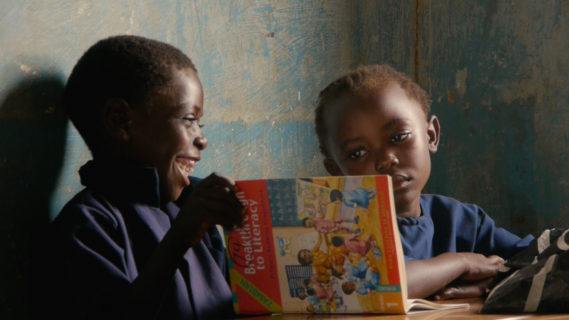 A photo of two children sitting next to each other, the boy smiles with an open book in his hands, while the girl looks over at him.