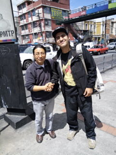 A photo of two people smiling at the camera and shaking hands on a city sidewalk.