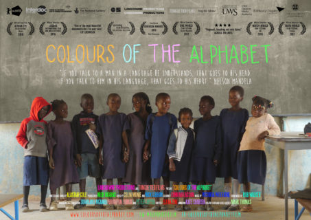"""Ten children stand in front of a chalkboard; some hold hands and look at each other, others look at the camera. Atop the photo is the movie title """"Colours of the Alphabet"""" and other text detailing the awards and crew associated with the movie."""