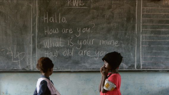 """Two children stand across from each other in front of a chalkboard with writing on it that reads """"Hallo, How are you? What is your name How old are you."""""""