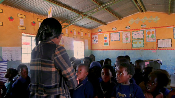 A photo of children facing the camera in a classroom with their teacher standing in front of them.