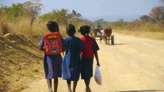 A photo of three children from behind walking down a dirt road.