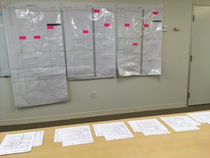 Five piles of paper lie on a table top in the foreground. Behind these three large pieces of paper hang on a wall. They are covered with a grid and marked with a few pink rectangular stickers.