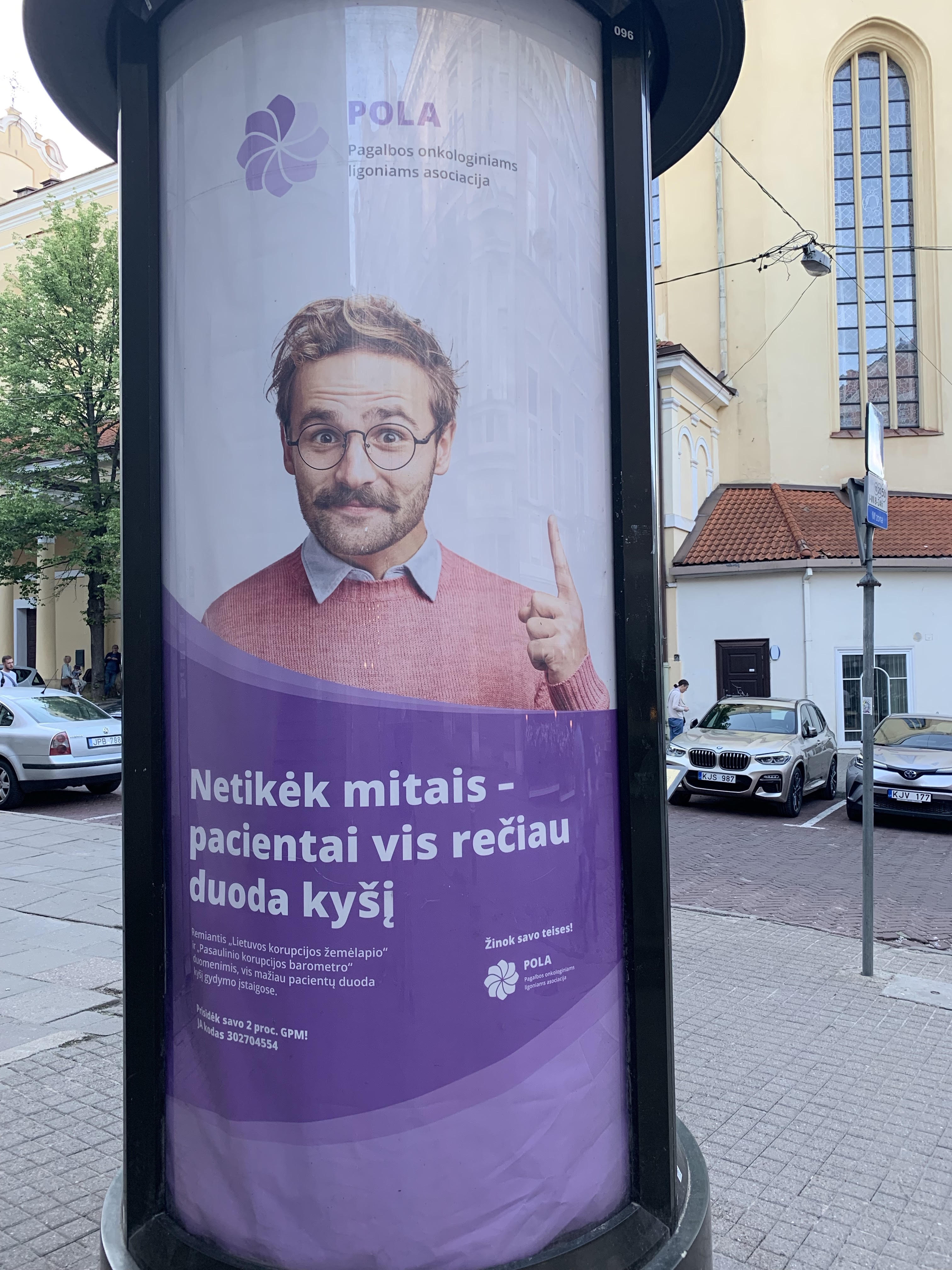 """Ad showing man wearing glasses and pointing his finger: """"Don't Believe the Myths – patients are giving bribes less frequently. Know your rights! Lithuanian Corruption Map data shows that fewer patients are giving bribes in health care institutions."""""""