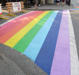 A photo of a crosswalk painted in colors of the rainbow.