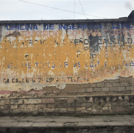 A damaged adobe wall that is completely covered with a faded sign with blue and black words and yellow and white background.
