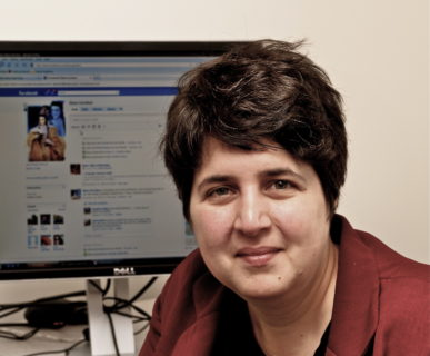 A photo of an individual with short brown hair smiling at the camera and sitting in front of a computer screen.