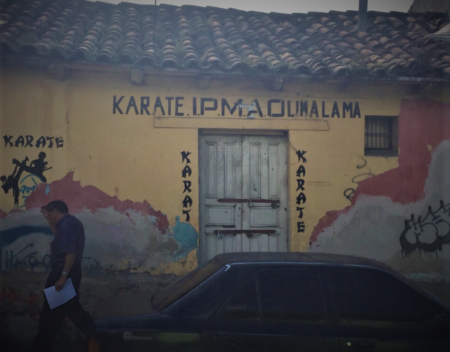 An old adobe and stucco building with a damaged tile roof that was the location of a karate studio.