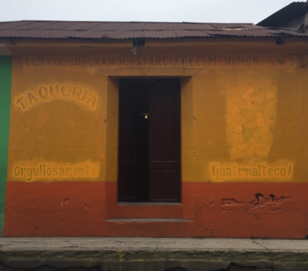 A yellow and red painted adobe building with the faded sign of a taco restaurant.