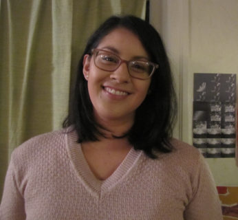 A photograph of a woman with dark shoulder-length hair wearing glasses and smiling.