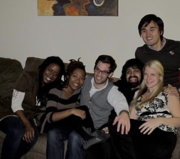 A photo of six people sitting on a couch leaning against each other and smiling.