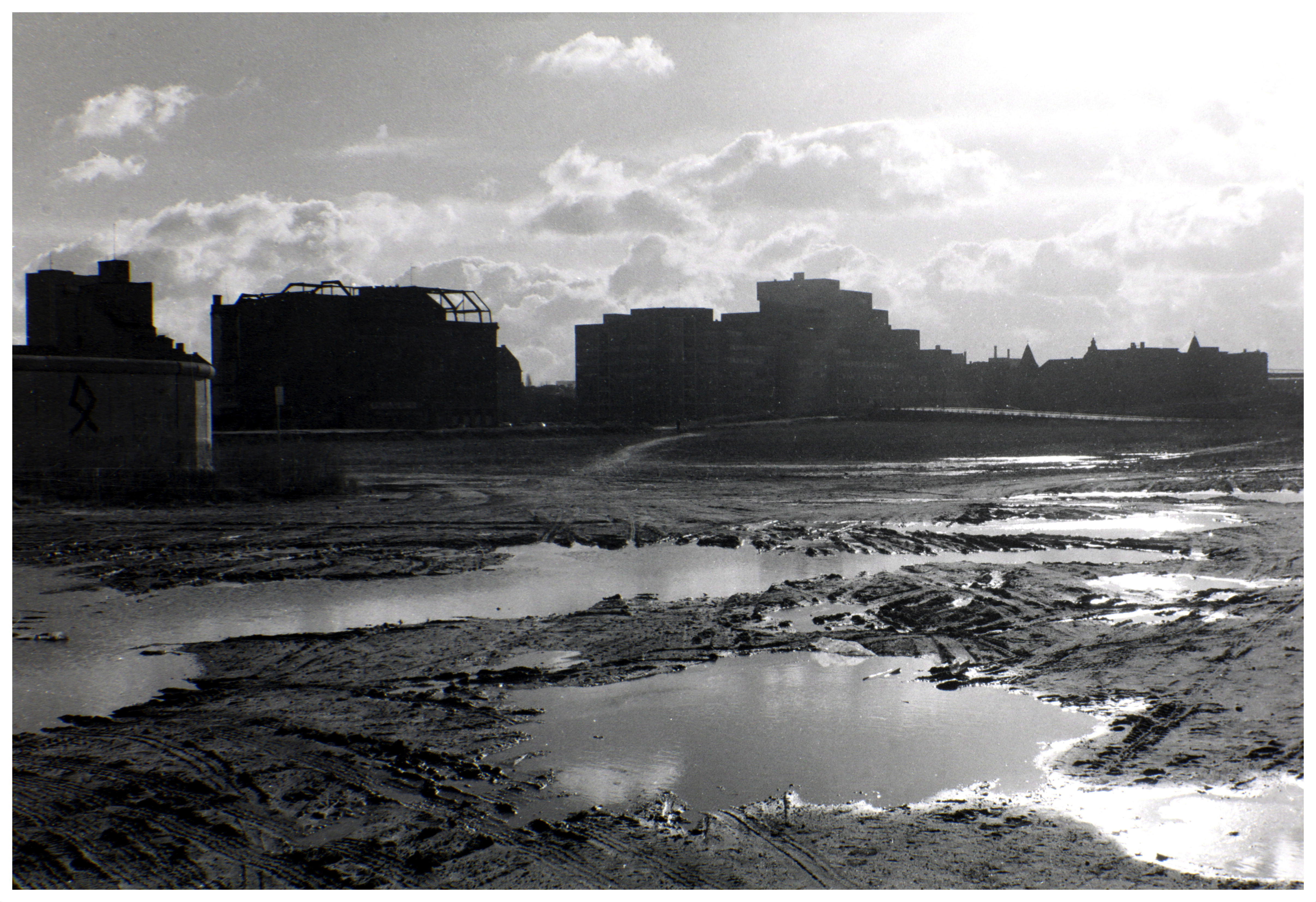 A black and white photo of an open, muddy area and buildings lining the horizon.