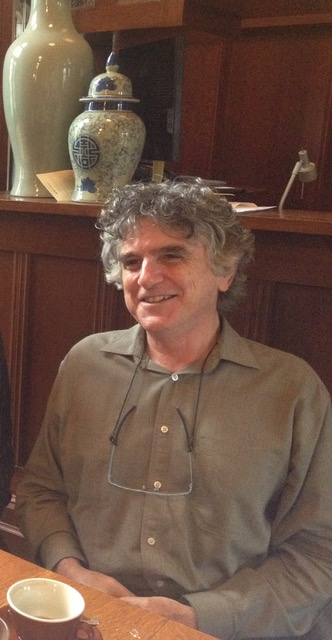 Photo of a person sitting at a table smiling.