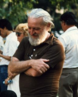 An image of C. Loring Brace: a tall white man with gray hair and beard, wearing a black t-shirt and standing with his arms crossed.