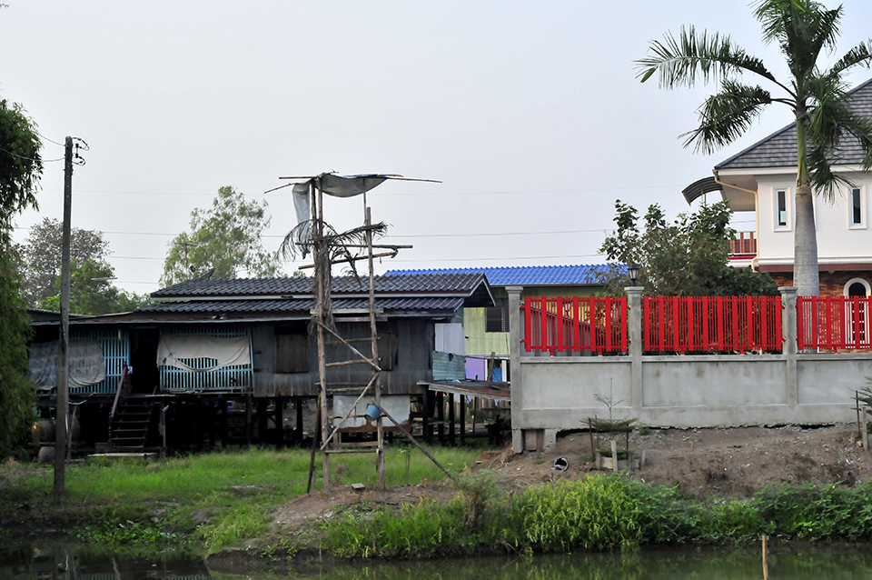 A photograph shows two homes side by side. The one on the left is made of wood and resting on stilts a few feet off the ground. The house on the left has a concrete or stone foundation and a red fence surrounds it. In the forefront, the edge of a body of water is visible.